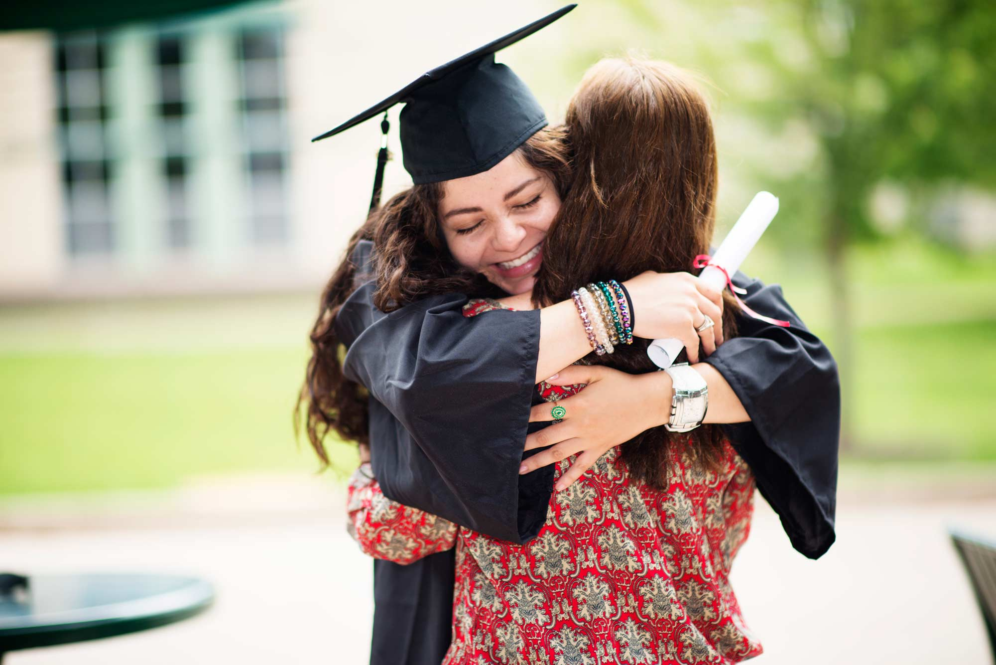 Graduate hugging woman